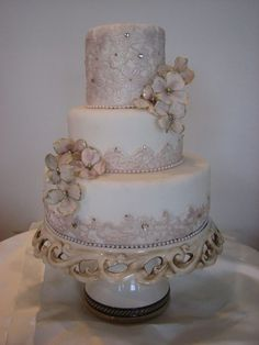 "* MAGGIE....an elegant and tasteful wedding cake with elements of fondant ""lace"", gumpaste blossoms and gems."