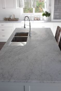 Carrera stone benchtop. Under mount sink. Breakfast bar. White cupboards.