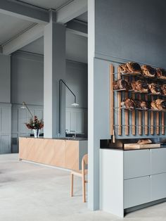 Reform's new showroom in Aarhus, Denmark. A space with monochrome grey walls and concrete floors. A cafe run by coffee roasters La Cabra. The space is with IKEA hack kitchens.