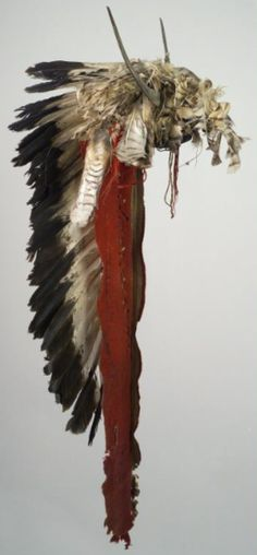 Buffalo Horn Bonnet, Crow or Arikara. ДА1. Date: 1860. Width of cap: 9 in. Catherine Bradford McClellan Collection.  Horn headdress - red wool cloth spine with tanned hide skull cap. Hawk feathers and split buffalo horns attached to skull piece with overlay bead decoration across front band with red string tassles on each side. Eagle feathers down center of trailer. Buffalo Bill Center of West.