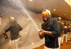 The Giants' Sergio Romo celebrates in the locker room after defeating the San Diego Padres 9-8 and clinching the wildcard in the National League West Division championship in baseball game in San Francisco, Thursday, Sept. 25, 2014. (AP Photo/Tony Avelar)