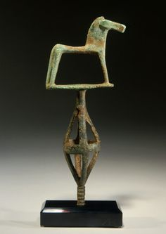GREEK GEOMETRIC BRONZE HORSE    Standing upon a plate supported by an open-worked bi-conical cage.    Macedon, late 8th-early 7th Century BC