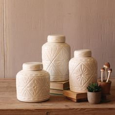 Storage with style. This trio of ivory-colored canisters is an eye-catching accent for shelves and countertops. Made from durable, glazed ceramic and imprinted with a unique geometric design. A lovely addition to your kitchen or living space.