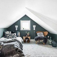 chambre mansardée, couleur mur bleu pétrole, tapis gris, couverture de lit gris, coussins en gris, blanc, noir et bleu, chaise en rotin, table de service en bois rustique