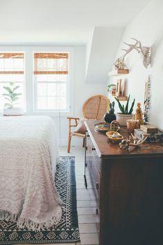 apartment bedroom, boho bedroom, wicker chair, blue rug, antlers