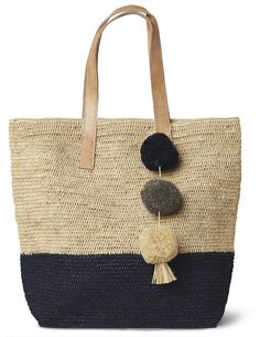 Navy Montauk Carryall Bag – Favery -- Perfect for the beach, the market, or zipping around town, this beautiful carryall bag, crocheted from sustainable sisal with a classic stripe, is adorned with festive raffia pom poms and features a cotton lining, snap closure, and durable leather handles.
