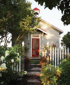 An iconic white picket fence and cheerful red trim frame the front door of a refurbished 19th-century schoolhouse. #little #house