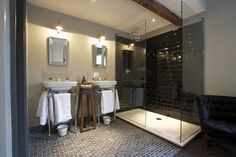 Contemporary bathroom features open shower with seamless glass walls accented with black subway tile shower surround and rain shower head next to beveled mirrors over his and her washstands flanking rustic table over black tiled floor laid out in brick formation.