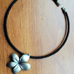 Silver Hawaiian Flower Cord Choker Necklace Materials unknown, silver colored pendant attached to choker style round cord, open at back, simply bend to put on, hold its shape. Very pretty! Urban Outfitters Jewelry Necklaces