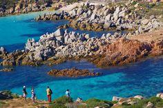 Tourists admiring blue waters of Corsica's coastline.