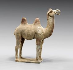 """TANG DYNASTY POTTERY CAMEL, painted pottery model of a Bactrian camel; with head thrown up showing expressive features; standing four-square on base, with much original pigments remaining; H: 20"""""""