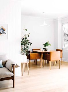 white walls brown leather chairs and wooden dining table in an open plan living rooms