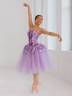 Forget Me Not dance costume on Revolution Dancewear: Lavender spandex leotard has front overlay of pink and purple sequin mesh and is trimmed with stretch sequins. Attached romantic length tutu has layers of light purple tulle under layers of lavender glitter tulle with a sequin mesh peplum.