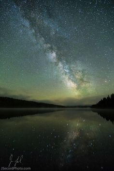 """In and Around the Lake"", the Milky Way glowing in the sky and reflecting in a lake at Lake Francis State Park in Pittsburg, New Hampshire; photo by Jon Secord"