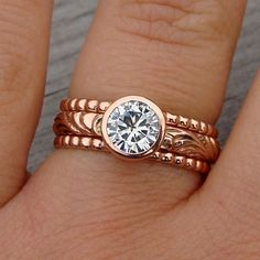 Moissanite and recycled 14k rose gold engagement/wedding rings. would bd perfect if band was all small diamonds