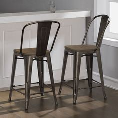 Designed with a vintage steel construction, this set of two counter stools feature solid elm wood seats with a weathered look. Whether your style is rustic, industrial, or transitional, these intricate chairs deliver a sleek appeal.