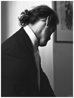 Posing for a black & white image, Sam Heughan rocks a man bun.
