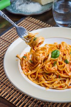 Roasted Red Pepper and Goat Cheese Alfredo Pasta:   1/2 pound pasta;   2 tablespoons butter;   1 clove garlic, grated;   1/2 cup heavy cream;   4 ounces goat cheese;   1/4 cup parmigiano reggiano (parmesan), grated;   2 roasted red peppers, coarsely chopped;   Salt and pepper to taste;   1 handful basil