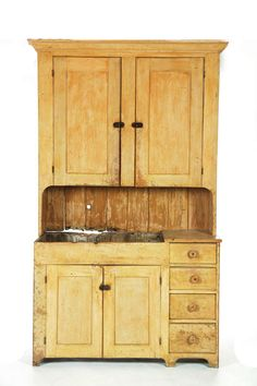 """PAINTED DRY SINK CUPBOARD.   American, mid 19th century, pine and poplar. Two-piece, the upper section with two doors, and the lower section with two doors and four drawers. Retains old yellow paint with a dry surface. 84 1/2""""h. 53""""w. 20""""d."""