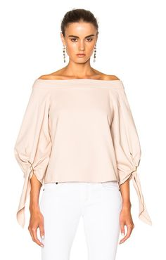 Off shoulder sculpted top by Tibi. 48% cotton 45% polyamide 7% elastan.  Made in China.  Dry clean only.  Buckled sleeves.