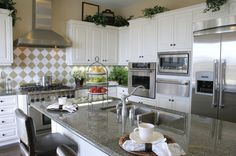 This beautiful white kitchen with grey marble tops has added interest through large white and grey harlequin backsplash and stainless steel exhaust hood.
