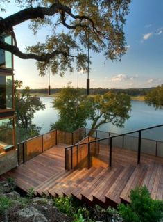 This modern multilevel deck has lights hanging above it at multiple levels. It seems to follow the varying heights of the trees, offering glimpses of the water from up high or down closer to the water.