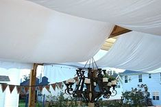 WHITE BEDSHEETS DRAPED OVER A PERGOLA TO LOOK LIKE BILLOWING SAILS