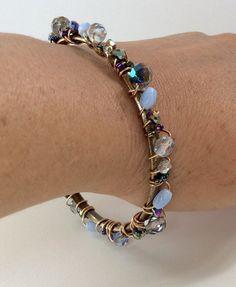 Bracelete ( de R$40 por R$30 ) . Círculo de metal ouro velho, envolto por arame importado ( copper wire ) e cristais, muranos e miçangas em tons de azul.