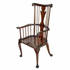 A very large 18th century style mahogany broad arm windsor chair. The windsor chair has a tall back with a scroll shape to the top rail, a broad splat with shaped mahogany spindles and a shaped seat.  The chair has cabriole Queen Ann legs to the front and similar kick out legs to the rear. The chair is made from very good quality mahogany and is in excellent original condition made at the turn of the 19th to 20th centuries