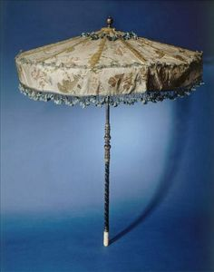 Asian-inspired parasol that features intricately detailed textiles and carved handle.  Handles could be made of wood or metal.