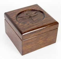 This handcrafted trinket box is constructed of quartersawn white oak. The lid features a relief carved dragonfly. The box measures 5 inches square by approximately 3-1/4 inches tall The finish has been distressed a bit to suggesst an aged piece.  Available for $70.00.