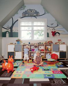 Architect Shamir Shah commissioned a fanciful mural by Malcolm Hill in Wainscott, New York, for the three sons of clients Julie and Bruce Menin; the playroom features cabinets by Blu Dot and carpet tiles by Flor.