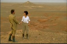 Justine Waddell in the final scene of the 1999 miniseries Wives and Daughters. Wearing menswear: white collared shirt and tan trousers with boots, in the desert