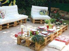 Salon de jardin composé d'une grande table basse en palette et de canapés confortables