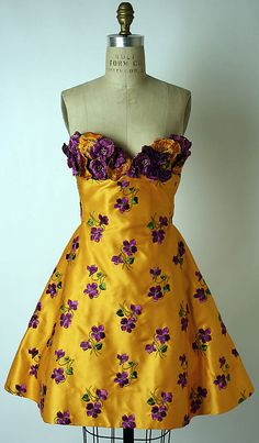 Yellow silk satin cocktail dress embroidered with violets, designed by Arnold Scaasi, American, fall/winter 1991-92. Part of an evening ensemble consisting of this dress and purple satin pumps designed by Charles Jourdan.