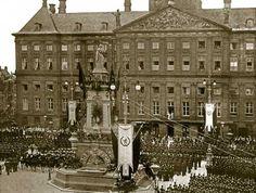 AMSTERDAM - Koningin-moeder Emma en prinses Wilhelmina worden op de Dam begroet door een grote menigte. De vorstinnen staan minutenlang op h...