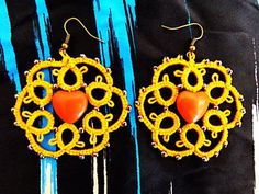 Circle shaped earrings with heart pearl made with tatting technique.