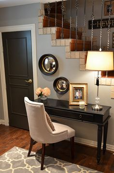 black door with gold hardware in white trim. Beautiful wood flooring. Pretty rug. Entry desk. My favorite-the stairs and railing