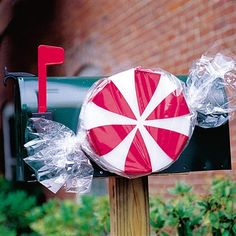 """Peppermint Mail Post  3 Styrofoam disks, 1"""" thick and 10"""" in diameter  Tacky glue  Red metallic ribbon  Scissors  Straight pins  Clear cellophane  Twist ties  Wire or twine"""