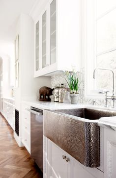 Tiled backsplash in white kitchen with stainless steel hardware and dishwasher