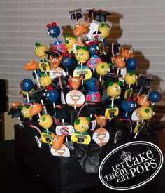 graduation cake pop display by LetThemEatCakePops.com  Three grads headed to three different colleges. I made the mortar boards with their high school logo on the stick tags, and then each of the college mascots–University of Texas Longhorns, Baylor Bears, and Belmont Bears.