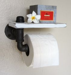 Maybe make a  wood and pipe toilet paper holder like this one from BeachCityCreations via Etsy.