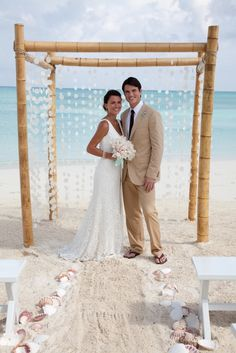 Beach Wedding arbor and strings of sand dollars AND shells line aisle which is a great touch.