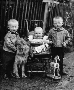 August Sander: Farm Children: 1920 The boy on the right, obviously the eldest, holds a toy whip erect like a staff, as though he already assumes his role as the leader of the group. Both of the older children position themselves as protective brothers to their infant sister, who sits in the carriage holding a doll. One brother rests his hand next to her on the carriage handle, while the other leans in toward her, possibly holding her hand behind the dog's head.