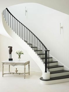 Staircase Design Ideas Flowing Staircase – Flowing down like the train of an elegant gown, this staircase creates a dramatic style statement. The dark wood treads and metal balustrade lend contrast to the otherwise all-white foyer. Modern Stair Railing, Wrought Iron Stair Railing, Stair Railing Design, Stair Handrail, Modern Stairs, Railing Ideas, Iron Railings, Staircase Railings, Curved Staircase