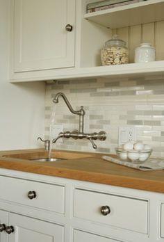 butcher block countertops + pretty marble tiles used as backsplash *love*