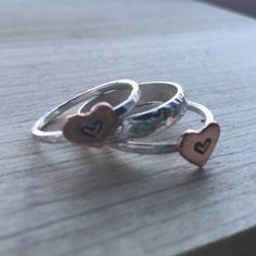 Delicate hand stamped copper hearts with a sterling silver band make a unique ring that can be worn on its own or stacked.