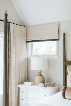 Neutral bedroom with whitewashed nightstand and a brown lamp, Aerin Gannet Lamp, placed under a window dressed in a cream roman shade. Kate Marker Interiors