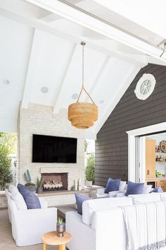 Hung from a high vaulted patio ceiling, a tiered woven basket chandelier lights side-by-side facing white slipcovered chairs topped with denim blue pillows and complementing a white slipcovered sofa. Sofa Design, Interior Design, Coastal Interior, Bar Interior, Patio Design, Outdoor Rooms, Outdoor Living, Outdoor Patios, Outdoor Kitchens