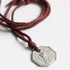 Regalo de Comunión - colgante Notre Dame. Original regalo para la Comunión de un chico. Cordón corredizo rojizo con medalla de hierro con el relieve de la iglesia de Notre Dame. En la parte de atrás grabamos el nombre o una fecha. Precio: 19,50 €